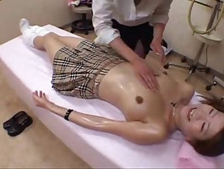 tall school girl is getting her tanned body massaged
